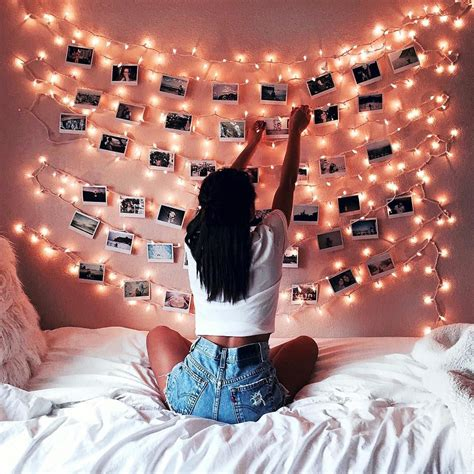 young woman bedroom and string lights decoration with fairy lights and photos on a pink wall