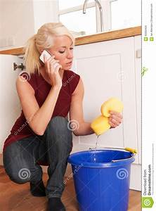 Plumber Woman Repairing De Pipe Of The Kitchen Royalty
