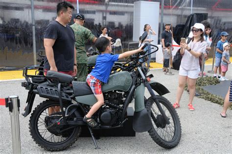 Visitors Exploring The Yamaha Tw200 Motorcycle At Army