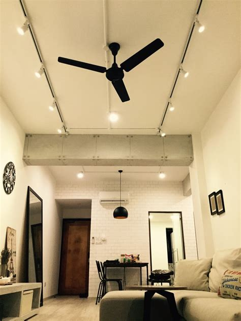 ceiling fan with track lighting living area shot from the floor concrete finished beams
