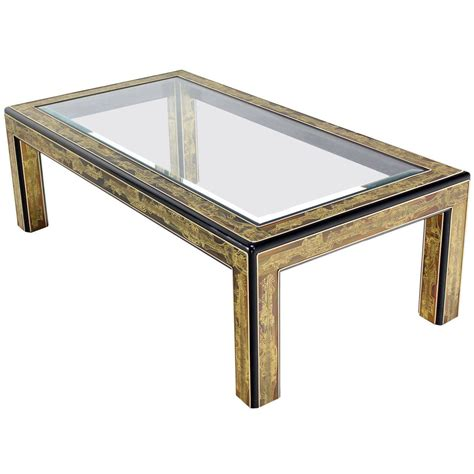 An asymmetric base elevates this round coffee table into a work of sculptural art. Rectangular Glass-Top Brass and Wood Base Coffee Table by Mastercraft at 1stdibs