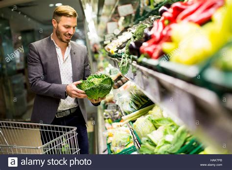 Young man buying vegetables in the supermarket Stock Photo ...