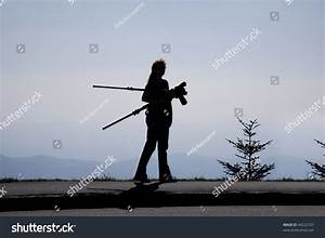 Silhouette Woman grapher Carrying A Tripod And