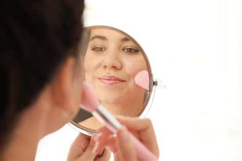 afro american woman applying makeup  brush stock photo