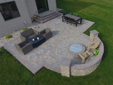 pit on patio raised deck to patio with fire pit and seat wall in west fargo nd oasis landscapes