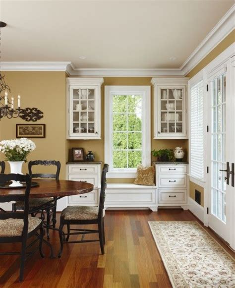 rich gold walls are complimented with white cabinets and warm woods room designs in