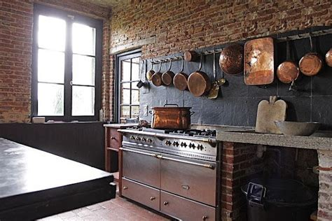 Kitchen with rough brick, copper pots and a stainless