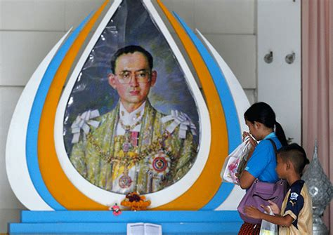 A Well Wisher Gestures In Front Of A Picture Of Thailand S King Bhumibol Adulyadej At Siriraj
