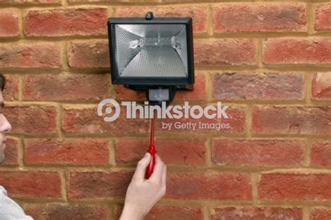 using terminal screwdriver to attach security light to brick wall stock photo thinkstock
