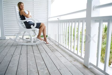 contemplative woman sitting  rocking chair  porch