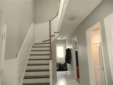 grey hallway with white brown staircase and white paneling