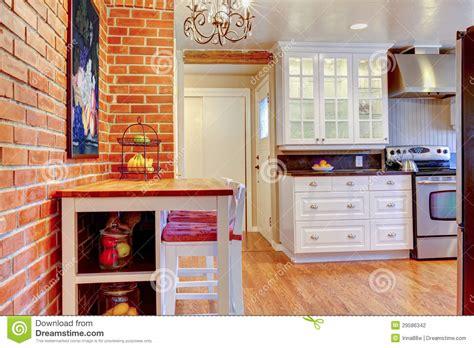 la cuisine blanche avec le mur de briques le bois dur et inoxydables volent le fourneau