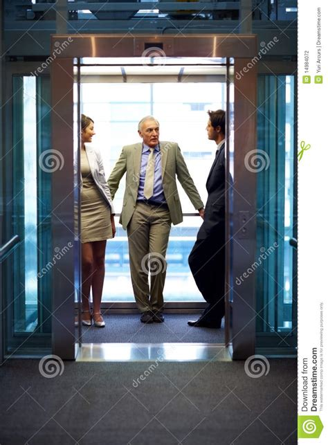 successful business people standing  elevator stock