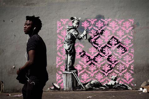 Street artist Banksy paints Paris with murals of migrants ...