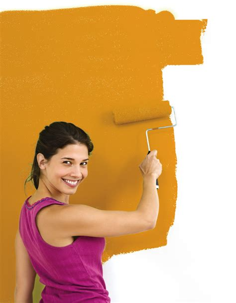 pretty smiling painting interior wall of home with paint roller