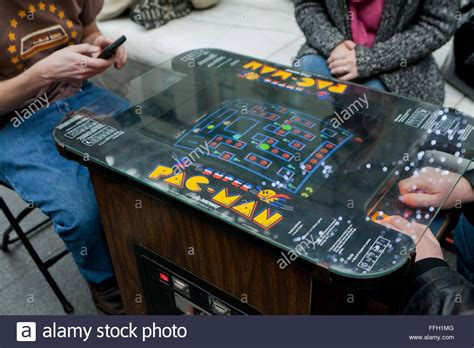 People Playing A Vintage Pac Man Video Arcade Game Usa