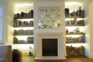 livingroom shelves exposed brick wall surround fireplace wit white mantel also white wooden cabinet shelves beside