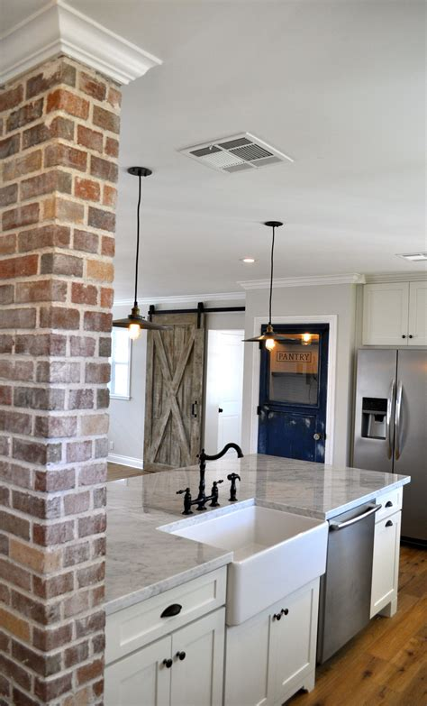 kitchen sink with marble top exposed brick farmhouse sink sliding barn wood door and
