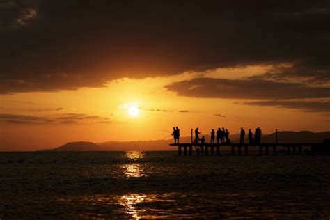 person  boat sailing  clear water  sunset  stock photo