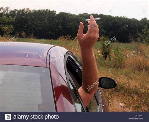 trou cigarette siege auto holding lit cigarette out car window during drive