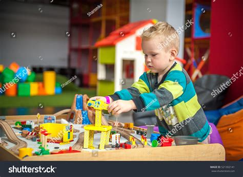 children play wooden build stock photo 521302141 617 | stock photo children play with wooden toy build toy railroad at home or daycare toddler boy play with crane 521302141