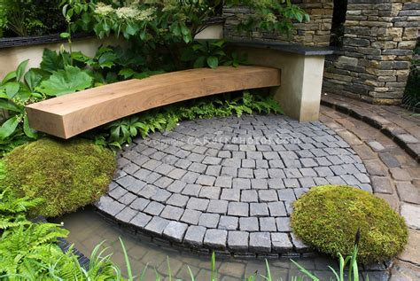 patio of bluestone pavers with curving bench moss ferns