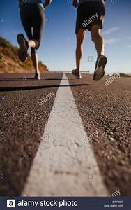 Cropped shot of two people running on road. Athletes ...
