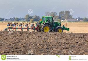 Tractor With Plough In The Field Stock Photo