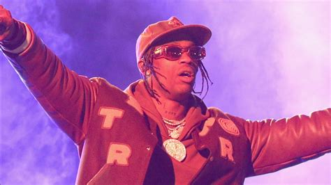 travis scott  wearing brown dress  cap gold chains