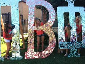 broken glass glued to large letters that were painted With large sorority letters