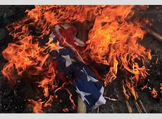 A burning US flag is seen on the ground after it was set