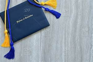 flat lay of a diploma of graduation with honor cords on a