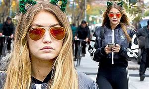 Gigi Hadid dresses up her sporty outfit with green feline ...