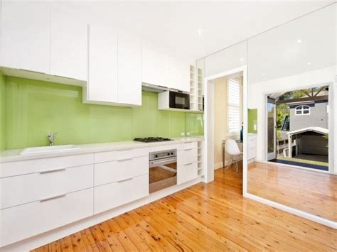 white kitchen with green glass splashback white kitchen and timber floors with a apple green 2105