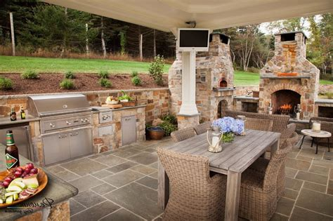 Wonderful Outdoor Kitchen In Brick Design With Rattan Dining Set And Fireplace