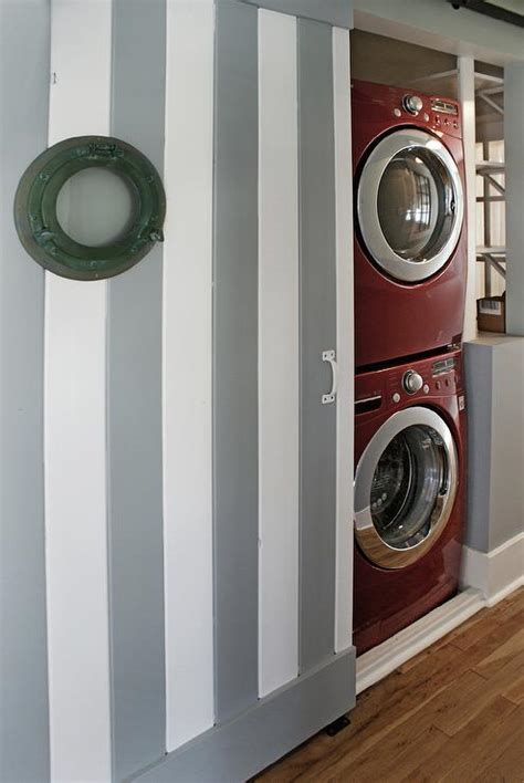 laundry door room washer dryer closet barn hallway sliding behind stacked coastal bath painted gray rustic striped located features window