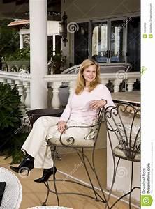 Mature Woman Relaxing On Patio Bar Stool Stock Photos
