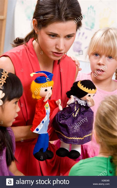storytelling children stock photos amp storytelling 557 | teacher with preschool children sitting in a circle playing with puppets X28D65