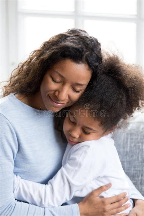 loving african american mother embracing with daughter