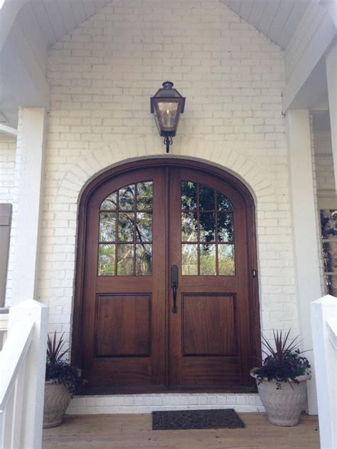 brown arched glass front door  white brick home