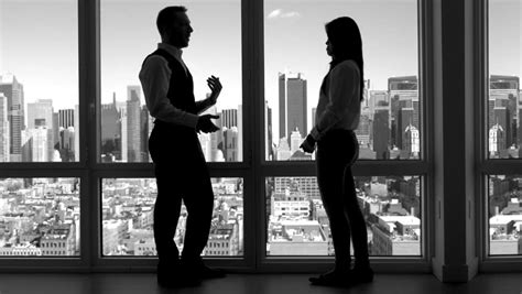 desk for two persons two business coworkers standing in front of window facing
