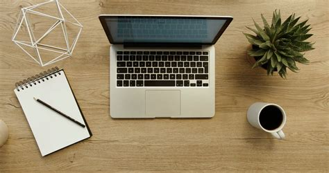 Office Desk Top View by Business Working And Writing In Laptop On Office Desk