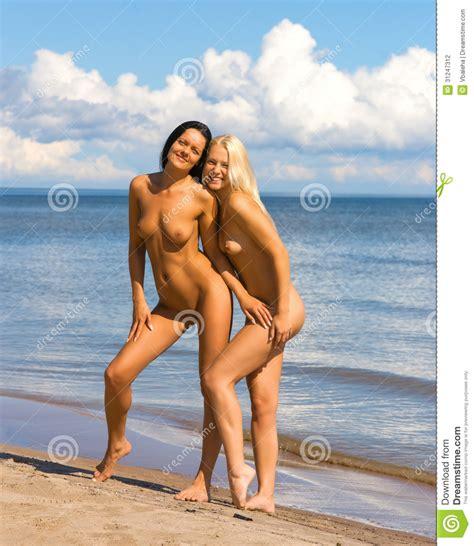 two nude women sunbathing on the beach stock photo image