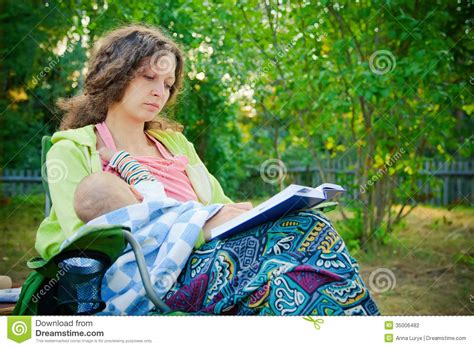 Mother Breastfeeding While Reading The Book Stock