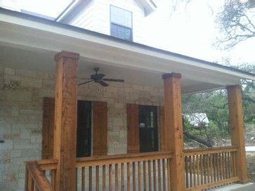 texas hill country stone home  cedar columns porch railings  cedar shutters  kurk