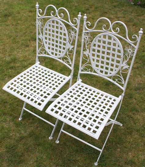 two white floral outdoor folding metal square chairs
