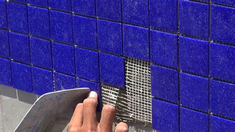 Pool Tile Installation, Laborer's Hands Installing Blue