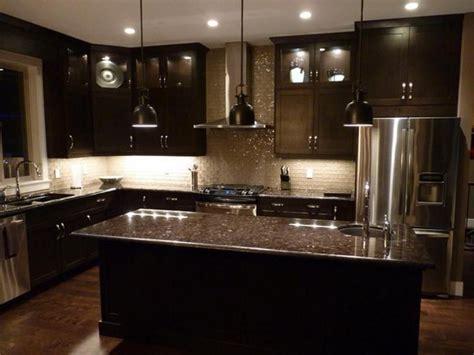 kitchens with black cabinets black glass tile backsplash brown iron chandelier white