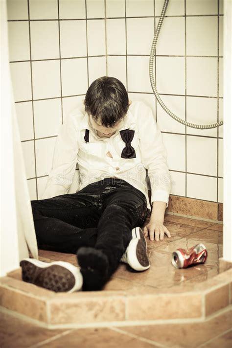 drunk young teenage boy asleep   shower stock photo