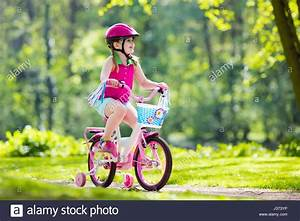 Child riding bike. Kid on bicycle in sunny park. Little ...